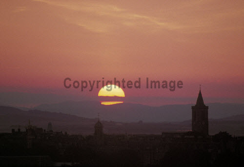 The sun sets behind the hills surrounding Dundee, with St. Andrews in the foreground, Fife.