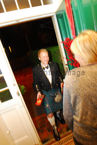 First footing on Hogmanay.Picture Credit: Chris Robson / Scottish ViewpointTel: +44 (0) 131 622 7174  Fax: +44 (0) 131 622 7175E-Mail : info@scottishviewpoint.comWeb: www.scottishviewpoint.comThis photograph cannot be used without prior permission from Scottish Viewpoint. 2010,new,year,years,eve,scotland,tartan,kilt,highland dress,gift,coal,whisky,shortbread,tall,dark,handsome,celebrate,event,january,winter,1st,kilts, people, men, boys, boy, happy, tradition, traditional, new, year, celebrations, celebrate,foot, firstfoot, firstfooting