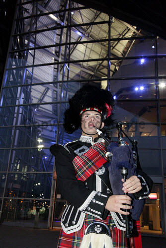 A piper at an event at the Armadillo / Clyde Auditorium, photographed at night, Glasgow.