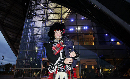 A piper at an event at the Armadillo / Clyde Auditorium, photographed at night, Glasgow. Picture Credit:  Iain McLean / Scottish Viewpoint Tel: +44 (0) 131 622 7174   Fax: +44 (0) 131 622 7175 E-Mail : info@scottishviewpoint.com Web: www.scottishviewpoint.com This photograph cannot be used without prior permission from Scottish Viewpoint. 2010,SECC,events,venue,concert,architecture,atmospheric,bagpipes,tartan,highland dress,kilt,conference