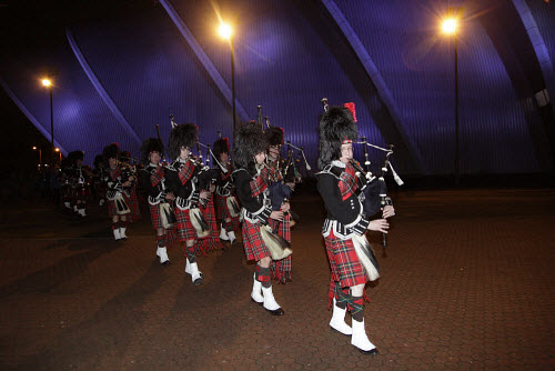 Pipers at an event at the Armadillo / Clyde Auditorium, photographed at night, Glasgow.