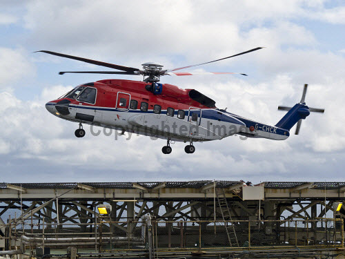 A Sikorsky S92 helicopter from Aberdeen carrying offshore oil workers arrives on an oil platform in the North Sea.