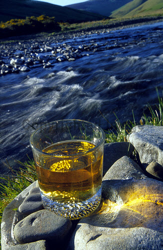 A GENERIC SHOT OF A GLASS OF WHISKY ON ROCKS BESIDE THE SIDE OF A RIVER.