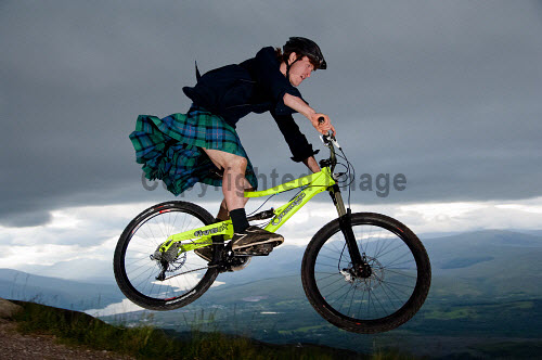 A kilted mountain biker at the Nevis Range Mountain Resort, Highlands of Scotland. activity,activities,cycling,cyclist,cyclists,bike,bikes,biking,biker,bikers,bicycle,bicycles,people,person,tartan,jump,jumping,kilt