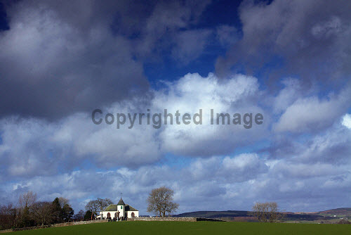 The view over fields to Balmaghie Parish Church, Balmaghie, Dumfries and Galloway. 2014,winter,spring,sunny,sunshine,Balmaghie,Church,kirk,Dumfries,Galloway,field,fields,cloud,clouds,building,architecture,grave,graves,graveyard,religion,sky