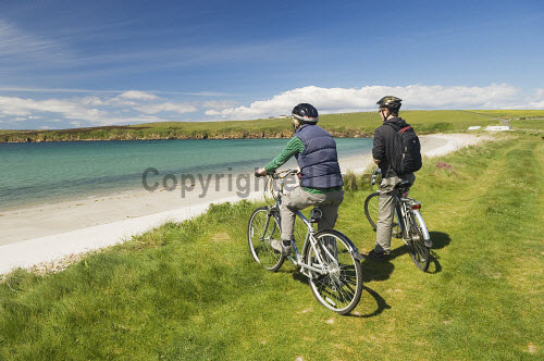 A couple cycling take in the view over Sands of Wright, South Ronaldsay, Orkney. Picture Credit : Iain Sarjeant / Scottish Viewpoint  Tel: +44 (0) 131 622 7174  E-Mail : info@scottishviewpoint.com  Web: www.scottishviewpoint.com This photograph cannot be used without prior permission from Scottish Viewpoint. 2012,summer,sunny,island,islands,isle,isles,activity,activities,cycling,cyclist,cyclists,bike,bikes,biking,biker,bikers,bicycle,bicycles,people,person,beach,sand,sandy,white,road