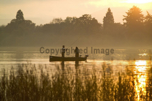 Two anglers fish from a small boat on the Lake of Menteith at sunset, Stirling District, Scotland. 2013,horizontal,sunset,evening,late,afternoon,autumn,Scotland,Scottish,UK,U.K,Great,Britain,autumnal,colours,activity,activities,anglers,angling,fish,fishing,fishermen,people,person,two,boat,Lake,Menteith,men,30-40,years,atmospheric,atmosphere,serene,peaceful,calm,rod,trees,reflection,reflections