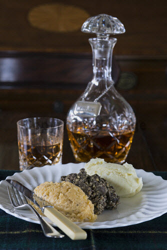 Haggis, potatoes and turnips with a glass and decanter of whisky in the background, Scotland. studio shot,indoors,nobody,food,eating,dining,dinner,haggis,turnips,potatoes,plate,sauce,tatties,neeps,uk,u.k,Great Britain,GB,G.B,Scotland,whisky,glass,whiskey,scotch,knife,fork,cutlery