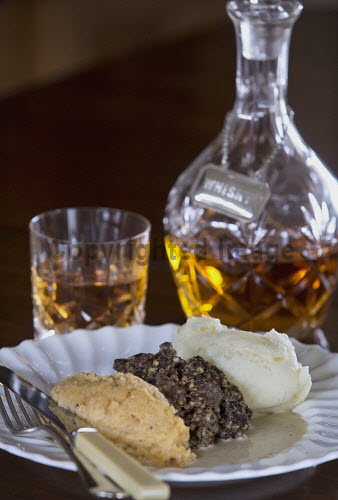 Haggis, potatoes and turnips in a whisky sauce with a glass and decanter of whisky in the background, Scotland studio shot,indoors,nobody,food,eating,dining,dinner,haggis,turnips,potatoes,plate,sauce,tatties,neeps,uk,u.k,Great Britain,GB,G.B,Scotland,whisky,glass,whiskey,scotch,knife,fork,cutlery
