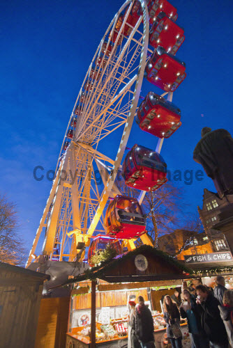 The Big Wheel in East Princes Street Gardens - part of Edinburgh's Christmas, in the city centre of Edinburgh. vertical,outside,outdoors,evening,dusk,night,winter,Big Wheel,fairground,East Princes Street Gardens,Edinburghs Christmas,city,Edinburgh,Scotland,Scottish,UK,U.K,Great Britain,people,xmas,lights,decorations,market,market stall,food,eating,fish and chips,cheese