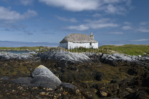 A traditional thatched cottage on the coast on North Uist, Outer Hebrides, Scotland North Uist,Outer Hebrides,uk,u.k,Great Britain,GB,G.B,Scotland,Scottish,Western Isles,nobody,outdoors,summer,sunny,island,islands,isle,isles,croft,blackhouse,tradition,thatched roof,crofts