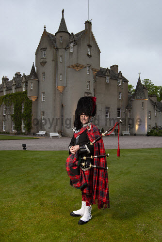 A piper in full Highland dress stands outside of Ballindalloch Castle, Ballindalloch, Moray, Scotland. vertical,outside,outdoors,exterior,summer,evening,Ballindalloch Castle,Moray,Scotland,Scottish,UK,U.K,Great Britain,one man only,1 person,attraction,building,piper,40-50 years,tartan,kilt,bagpipes