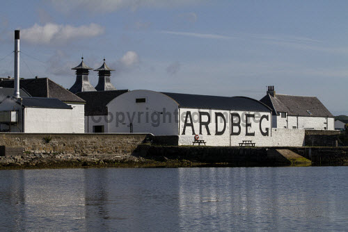 The Ardbeg Distillery on the Isle of Islay, Inner Hebrides, Scotland. horizontal,outside,outdoors,exterior,summer,day,Ardbeg Distillery,Islay,Inner Hebrides,Argyll,Scotland,Scottish,UK,U.K,Great Britain,nobody,attraction,building,single malt,whisky,production,coast,coastal,coastline,water,sea,reflection,calm,isle,island