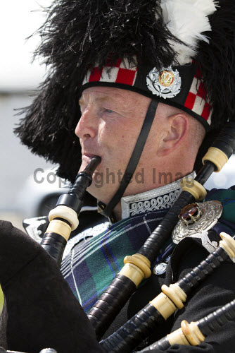 A piper in full Highland dress, Scotland. vertical,outside,outdoors,exterior,summer,Scotland,Scottish,UK,U.K,Great Britain,one man only,1 person,50-60 years,piper,tartan,bagpipes