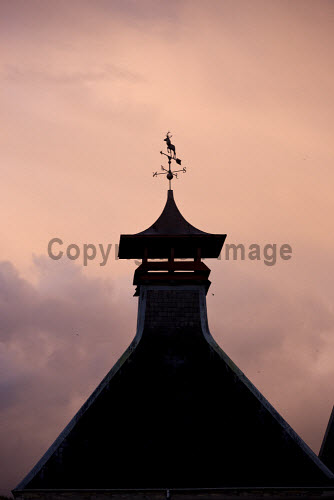 A detail of the pagoda at the Glenfiddich distillery - a Speyside single malt Scotch whisky distillery in Dufftown, Moray, Scotland. vertical,outside,outdoors,exterior,summer,evening,dusk,sunset,sunny,Glenfiddich Distillery,Dufftown,Moray,Scotland,Scottish,UK,U.K,Great Britain,nobody,attraction,building,single malt,whisky,production,Speyside,countryside,detail pagoda,weather vane,silhouette