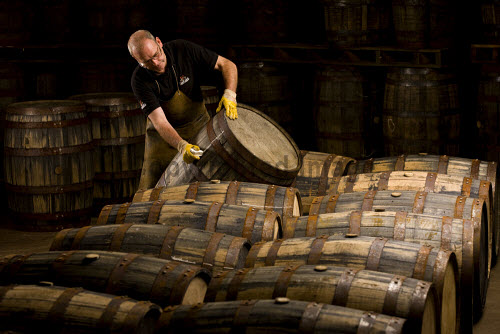 A worker with whisky barrels in  Glenfiddich distillery - a Speyside single malt Scotch whisky distillery in Dufftown, Moray, Scotland. horizontal,inside,interior,indoors,Glenfiddich Distillery,Dufftown,Moray,Scotland,Scottish,UK,U.K,Great Britain,1 person,one man only,45- 55 years,single malt,whisky,production,cask,barrels,worker,speyside