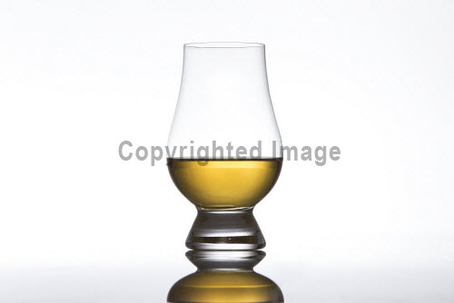 Whisky in a glass on a white background vertical,Scotch,whisky,glass,pour,pouring,white background,studio,set up,product,nobody,Scotland,Scottish,UK,U.K,Great Britain,cut out