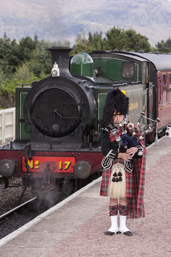 A piper playing the bagpipes at Aviemore Station with a steam train from the Strathspey Railway visible behind, Highlands of Scotland. vertical,outside,outdoors,exterior,summer,day,station,Aviemore,Strathspey Railway,heritage,steam train,engine,locomotive,Highlands,Scotland,Scottish,UK,U.K,Great Britain,one man only,1 person,40-50 years,full length,looking at camera,piper,bagpipes,tartan,kilt