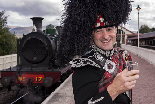 A piper with a dram of whisky at Aviemore Station with a steam train from the Strathspey Railway visible behind, Highlands of Scotland. horizontal,outside,outdoors,exterior,summer,day,station,Aviemore,Strathspey Railway,heritage,steam train,engine,locomotive,Highlands,Scotland,Scottish,UK,U.K,Great Britain,one man only,1 person,40-50 years,head and shoulders,looking at camera,smile,piper,tartan,glass,dram,whisky