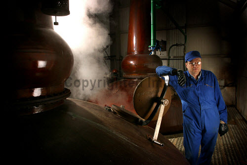 A distillery worker in the stillroom at the Tomatin Distillery - a Highland single malt Scotch whisky distillery, Tomatin, Highlands of Scotland. horizontal,inside,interior,indoors,Tomatin Distillery,Tomatin,Highland,Scotland,Scottish,UK,U.K,Great Britain,1 person,one man only,40-50 years,single malt,whisky,blended,Speyside,spirit,whiskey,stillroom,still,room,atmospheric,process,production,manufacture