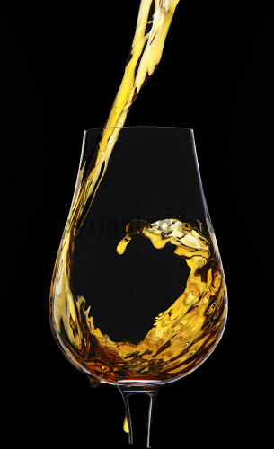 A traditional Scottish Whisky nosing glass with whisky being poured in to it. vertical,Scotch,whisky,glass,pour,pouring,black background,studio,set up,product,nobody,Scotland,Scottish,UK,U.K,Great Britain