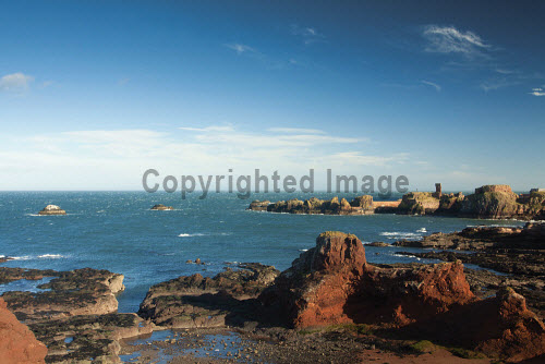 The view to the harbour and ruins of Dunbar Castle from the John Muir Way, Dunbar, East Lothian, Scotland. horizontal,outdoors,outside,day,winter,sunny,sunshine,blue sky,East Lothian,Dunbar Castle,The John Muir Way,walking,Dunbar,nobody,coast,coastal,coastline,water,sea,Scotland,Scottish,UK,U.K,Great Britain,rocks,ruin,ruins,ruined,heritage
