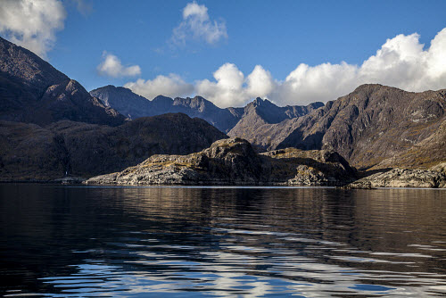 The view over Loch Scavaig towards the Cuillins, Isle of Skye, Inner Hebrides, Scotland. horizontal,outdoors,outside,autumn,sunny,sunshine,blue sky,skies,day,no people,nobody,Scotland,Scottish,UK,U.K,Great Britain,Highlands,mountains,cuillin,cuillins,Loch Scavaig,island,isle,Skye,Inner Hebrides,Highland,coast,coastal,coastline,water,sea