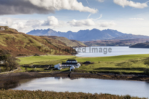 Farm buildings on Loch Bracadale with the Cuillins in the distance, Isle of Skye, Inner Hebrides, Scotland. horizontal,outdoors,outside,autumn,sunny,sunshine,day,no people,nobody,Scotland,Scottish,UK,U.K,Great Britain,Highlands,mountains,cuillin,cuillins,dramatic,island,isle,Skye,Inner Hebrides,Highland,coast,coastal,coastline,water,sea,farm,buildings,Loch Bracadale