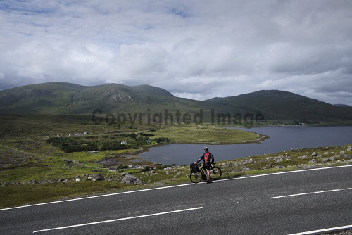 A cyclist on the road,  Isle of Harris,  Outer Hebrides, Scotland. uk,u.k,Great Britain,GB,G.B,Scotland,Scottish,1 person,daytime,outdoors,Outer Hebrides,western isles,cycling,cyclist,cyclists,bike,bikes,biking,biker,bikers,bicycle,bicycles,Harris,island,islands,isle,isles