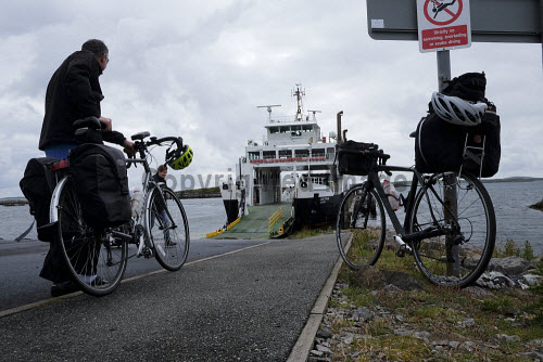 A cyclist on the  Isle of Harris at Leverburgh boarding the ferry,  Outer Hebrides, Scotland. uk,u.k,Great Britain,GB,G.B,Scotland,Scottish,2 people,daytime,outdoors,Outer Hebrides,western isles,cycling,cyclist,cyclists,bike,bikes,biking,biker,bikers,bicycle,bicycles,Harris,island,islands,isle,isles,caledonian,macbrayne,cal,mac,calmac,ferry,ferries,transport,travel,travelling,boat