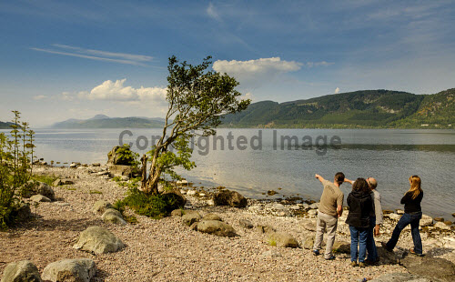 Tourists looking over Loch Ness from the eastern shore near Foyers, Highlands of Scotland uk,u.k,Great,Britain,GB,G.B,Scotland,Scottish,4 people,daytime,outdoors,summer,Highlands of Scotland,Loch Ness,coast,coastal,coastline,water