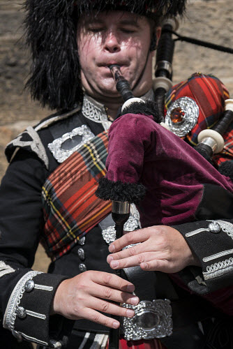 Detail of man playing bagpipes for tourists wearing traditional military uniform with tartan and kilt in Edinburgh, Scotland, united Kingdom Bagpiper,Scotland,playing,man,bagpipes,Scottish,musician,tartan,traditional,dress,clothes,male,music,heritage,culture,kilt,travel,tourism,Edinburgh