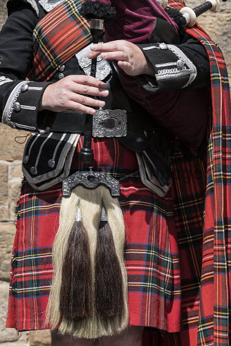 Detail of man playing bagpipes wearing traditional military uniform with tartan and kilt in Edinburgh, Scotland, united Kingdom Bagpiper,Scotland,playing,man,bagpipes,Scottish,musician,tartan,traditional,dress,clothes,male,music,heritage,culture,kilt,travel,tourism,Edinburgh