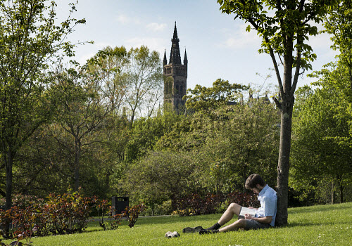 Student reading in Kelvingrove Park with Glasgow University to rear in Glasgow, Scotland, United Kingdom Glasgow,Kelvingrove,park,university,student,parks,reading,studying,Scotland,Scottish,higher,education,universities,daytime,outdoors,city,cities,1 person,Britain,British,united,Kingdom,Europe,European,male,man