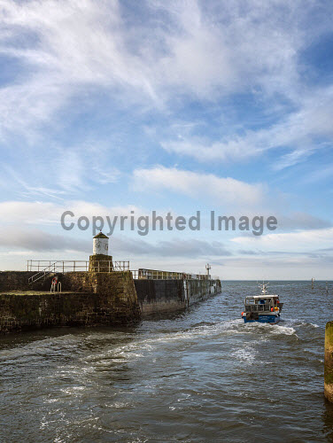 Fishing boat, and Harbour wall with lighthouse, in the pretty fishing village of Pittenweem on the coast of Fife. Scotland uk,u.k,Great Britain,GB,G.B,Scotland,Scottish,nobody,daytime,outdoors,harbour,wall,lighthouse,boat,fishing,fish,east neuk,industry,pittenweem,village,coast,coastal,fife,waterfront