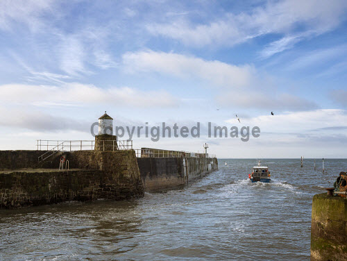 Fishing boat, and Harbour wall with lighthouse, in the pretty fishing village of Pittenweem on the coast of Fife. Scotland uk,u.k,Great Britain,GB,G.B,Scotland,Scottish,nobody,daytime,outdoors,harbour,wall,lighthouse,boat,fishing,fish,east neuk,industry,pittenweem,transport,transportation,travel,sail,village,coast,coastal,fife,waterfront