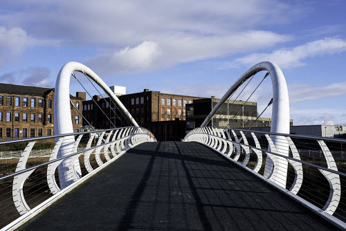 View of modern Clyde Gateway Bridge  crossing River Clyde at Shawfield in East End of Glasgow, Scotland, United Kingdom Glasgow,Shawfield,footbridge,River Clyde,modern,Clyde Gateway,pedestrian,Scotland,Scottish,East end,Glasgow east end,modern footbridge,new,UK,united Kingdom,Britain,British,transport,infrastructure,regeneration development,crossing,route,nobody,daytime,city,urban,planning