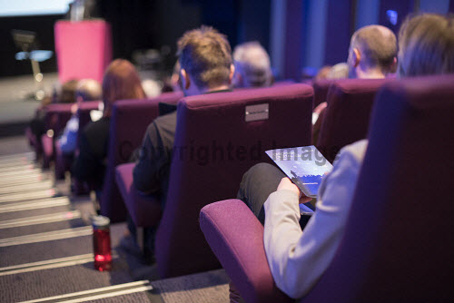 Audience member reading a brochure in a conference centre  Picture Credit John Paul / HIE DiscoverDigital 2016,Conference,conferences,conventions,convention,meeting,meetings,seats,seat,seating,2016,exhibition,exhibitions,expo,chair,chairs,delegate,delegates,audience,audiences,digital,#DiscoverDigital,#HelloDigital