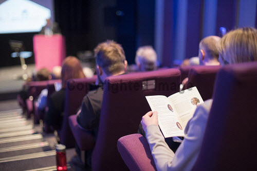 Audience member reading a brochure in a conference centre