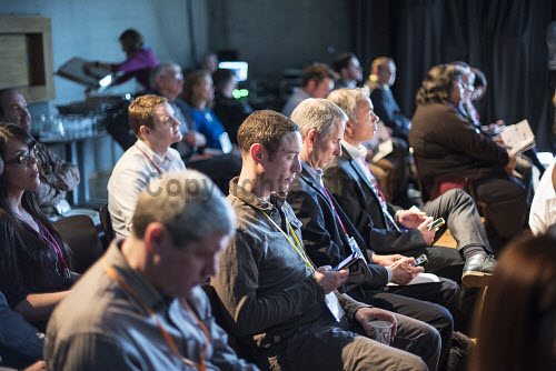 Audience members listening to a speaker and one member working on his mobile phone in a conference centre  Picture Credit John Paul / HIE DiscoverDigital 2016,Conference,conferences,conventions,convention,meeting,meetings,seats,seat,seating,2016,exhibition,exhibitions,expo,chair,chairs,delegate,delegates,audience,audiences,digital,#DiscoverDigital,#HelloDigital