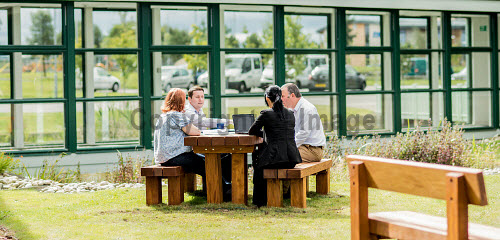 Stock Photography around Enterprise Park Forres, August 2013.  Here, people taking advantage of the new outdoor seating space and petanque area at Horizon Scotland.  Suitable for both meetings and lunch.