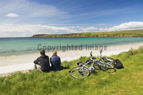 A couple cycling take in the view at Sands of Wright, South Ronaldsay, Orkney..Picture Credit : Iain Sarjeant 2012,summer,sunny,island,islands,isle,isles,activity,activities,cycling,cyclist,cyclists,bike,bikes,biking,biker,bikers,bicycle,bicycles,people,person,beach,sand,sandy,white,road,scenic