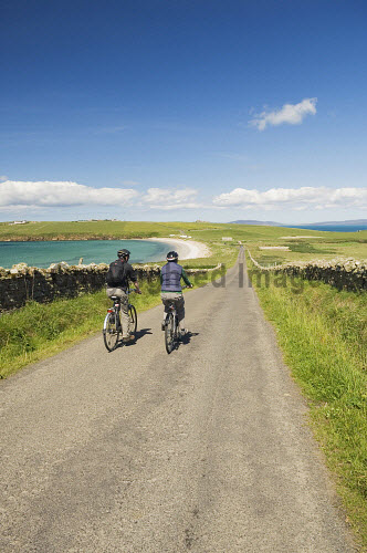A couple cycling near Sands of Wright, South Ronaldsay, Orkney..Picture Credit : Iain Sarjeant 2012,summer,sunny,island,islands,isle,isles,activity,activities,cycling,cyclist,cyclists,bike,bikes,biking,biker,bikers,bicycle,bicycles,people,person,beach,sand,sandy,white,road,scenic