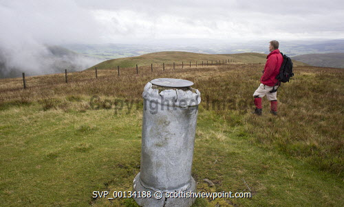 At the viewpoint indicator on top of East Mount Lowther mist rising out of Enterkin Pass, looking down Nithsdale, Scotland walk,walking,walker,climb,climber,outdoors,fresh,air,hill,hills,mountain,mountains,Lowther,rolling,heather,bracken,Mennock,Pass,Water,male,red,jacket,middle,aged,fit,fitness,health,healthy,Nithsdale,uk,u.k,Great Britain,GB,G.B,Scotland,Scottish,1 person,Dumfries,and,Galloway,ridge,misty,autumn,autumnal,gold,Wanlockhead,ancient,path,track,old,view,steep,East,Mount,top,peak,Enterkin,mist,viewpoint,indicator
