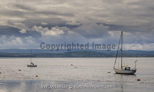 A calm and peaceful Findhorn Bay in Moray, Scotland at dawn on an April morning uk,u.k,Great Britain,GB,G.B,Scotland,Scottish,nobody,daytime,outdoors,Findhorn,Findhorn Bay,Moray,Moray Firth,anchorage,boats,calm,dawn,deserted,early morning,fishing port,idyllic,inlet,moored,mooring,north of Scotland,peaceful,spring,springtime,yachts,coast,coastal,coastline,water,sea