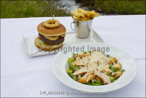 A burger and chips and chicken salad 
