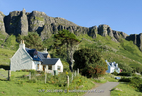 Houses on Isle of Eigg, with the Scaur, escarpment, Inner Hebrides uk,u.k,Great Britain,GB,G.B,Scotland,Scottish,nobody,daytime,outdoors,summer,restful,remote,peaceful,tranquil,bright,sunny,colourful,island,community owned,Isle of Eigg Community,eigg,small isles,west coast,lochaber,laig bay,cottages,farmhouse,houses,fence,village,hamlet,road,rocks,hillside,cliff,escarpment,scaur