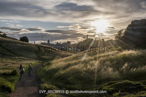 A couple enjoying the dramatic light across Holyrood Park looking to Calton Hill, Edinburgh