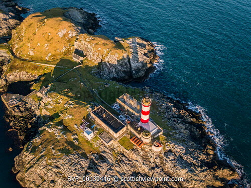 An Aerial photograph overlooking Eilean Glas Lighthouse on the Isle of Scaplay, Outer Hebrides, Scotland Spring,aerial,aerial photograph,architecture,bay,beautiful,blue sky,building,coast,coastal,coastline,drone,eilean glas,hebridean isles,isle of harris,lighthouse,outer hebrides,remote,rugged,rugged coastline,scalpay,scenery,scenic,scotland,scottish,scottish coast,seascape,shoreline,sunny,uk