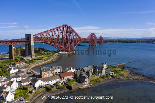 Aerial view of Forth Bridge crossing the River Forth and village of North Queensferry, Fife, Scotland, UK Forth Bridge Scotland,Forth Railway bridge Scotland,North Queensferry,Fife,Scotland,Scottish bridge,landmark,industrial heritage,UK,United Kingdom,britain,british,daytime,aerial view,drone,image,Firth of Forth,travel,tourism,bridges,railway bridge,historic,Forth Bridge at North Queensferry